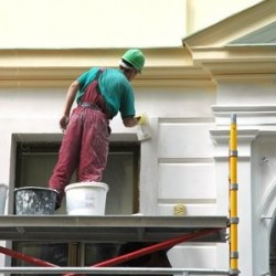 Man painting the outside of a building