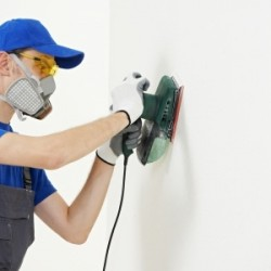 Man in mask removing lead paint